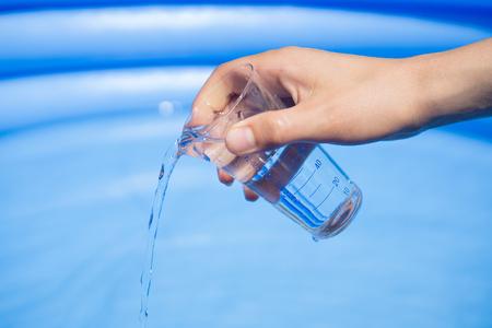 balanza de laboratorio: Las pruebas de agua en la piscina, laboratorio de vidrio con agua en la mano de la mujer