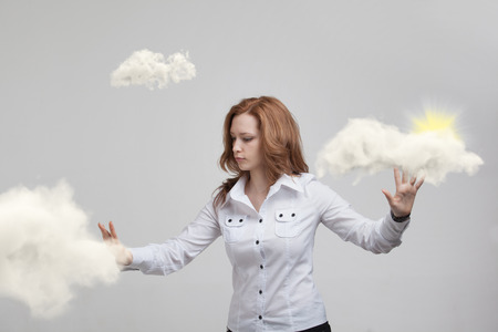 hopefulness: Young woman and sun shining out from behind the clouds, cloud computing or weather concept on grey background