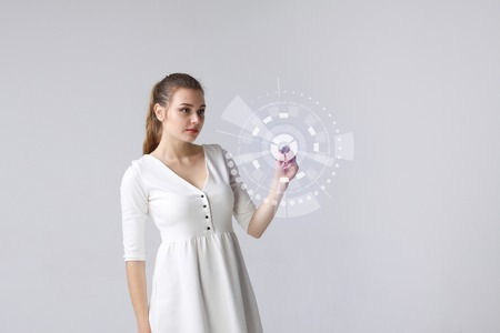 Future technology. Woman working with HUD futuristic interface on grey background.