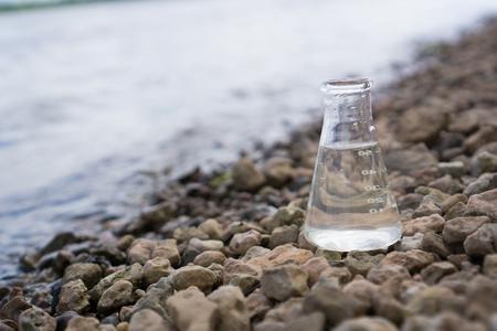 Wasser Purity Test. Chemische Flasche mit Wasser, See oder Fluss im Hintergrund. Standard-Bild