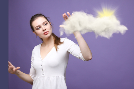 airiness: Young woman and sun shining out from behind the clouds, cloud computing or weather concept on violet background
