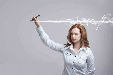 copywriting: Young woman making magic effect - flash lightning. The concept of copywriting or writing. Stock Photo