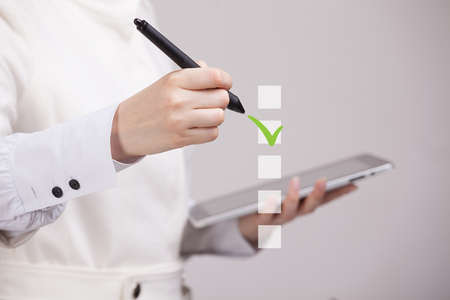 electronic voting: Young business woman checking on checklist box. Gray background. Concept on the topic of elections
