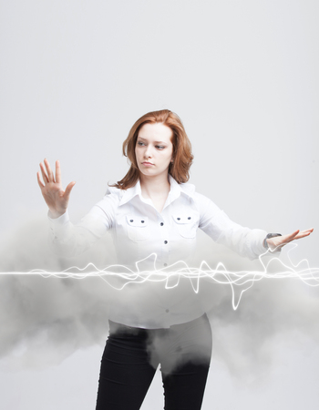 trickery: Young woman making magic effect - flash lightning. The concept of electricity, high energy. Stock Photo