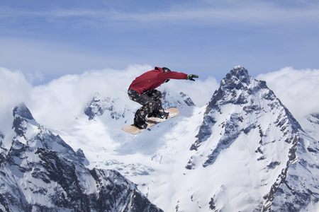 Snowboarder jumps high in the snowy mountains.