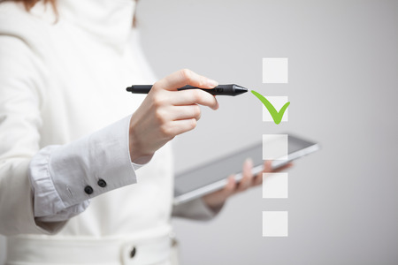 electronic survey: Young business woman checking on checklist box. Gray background. Concept on the topic of elections