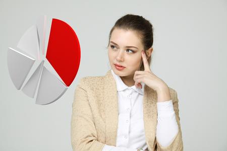 Giovane donna di affari mostra un grafico a torta (schema cerchio) su sfondo grigio. concetto di business analytics.