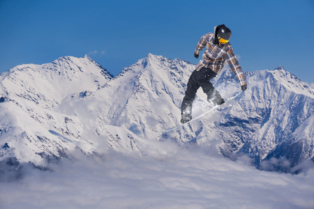 Snowboarder jumps on snowy mountain. Extreme winter sport. Stock Photo