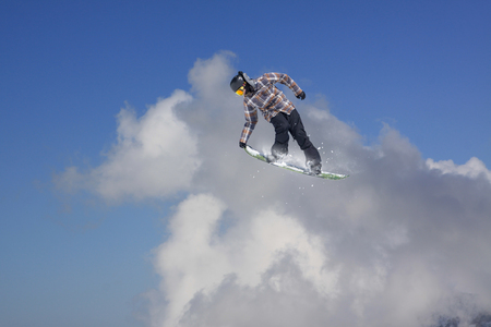 snowboarder jumping: Snowboarder jumping in mountains, extreme winter sport.
