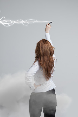Young woman with pen or stylus making magic effect - flash lightning. The concept of copywriting or writing.