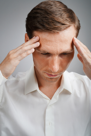 headaches: Young businessman in white shirt thinking or experiencing headaches, on grey background. Stock Photo