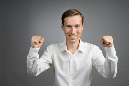 arms lifted up: Gesture of success. Happy smiling businessman in white shirt with raised hands. Half-length portrait. Stock Photo