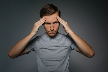 headaches: Young man in t-shirt thinking or experiencing headaches, on grey background.