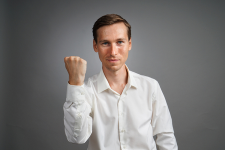 hands lifted up: Gesture of success. Happy smiling businessman in white shirt with raised hand. Half-length portrait. Stock Photo