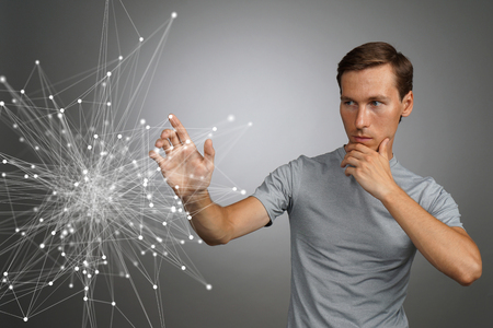 linked hands: Young man in t-shirt working with linked dots on grey background. Wireless connection or global network concept.
