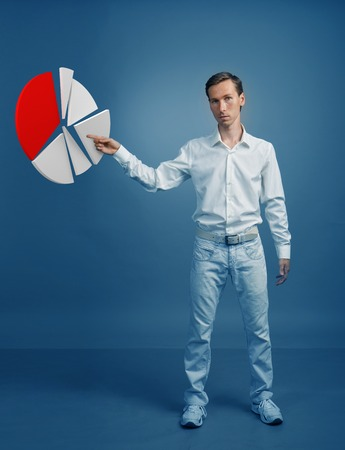 Young man in white shirt working with pie chart on blue background. Concept on the topic of statistics or financial report.