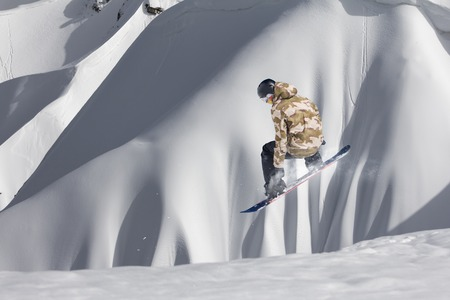 Snowboarder jumping on winter mountains. Extreme freeride sport.