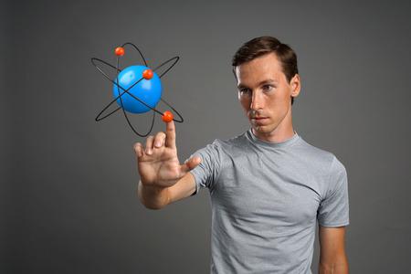 Giovane scienziato uomo con il modello dell'atomo, concetto di ricerca