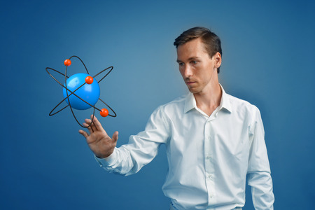 Young man scientist with atom model, research concept on blue background. Stock Photo
