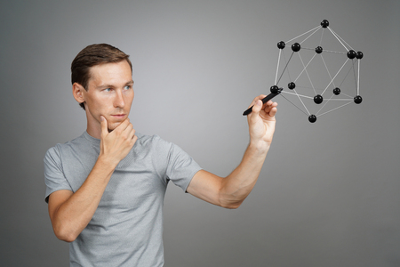 Young man scientist working with model of molecule or crystal lattice on grey background.
