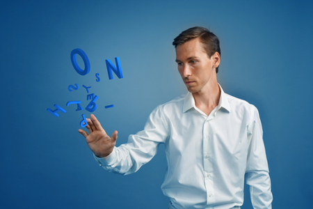encode: Young man in white shirt working with a set of letters on blue background, writing concept. Stock Photo