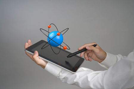 corpuscle: Man scientist holding a tablet PC with atom model, research concept on grey background