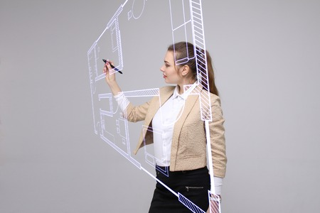 Female architect working with a virtual apartment plan. Virtual house design software. Stock Photo