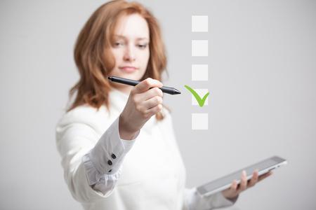 Młoda kobieta biznesu sprawdzania na polu listy kontrolnej. Szare tło. Praca na temat wyborów