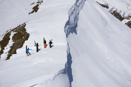 Snowboarders walking uphill for freeride, extreme winter mountaineering sport