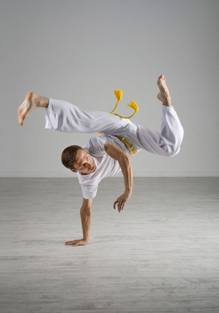 acrobatics: Young Man practicing Capoeira (brazilian martial Art with Elements of Dance, Acrobatics and Music). Stock Photo