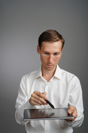 stylus: Man in the white Shirt working on Tablet with Stylus