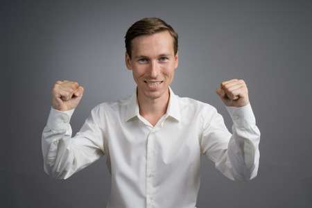 lifted hands: Gesture of success. Happy smiling businessman in white shirt with raised hands. Half-length portrait. Stock Photo