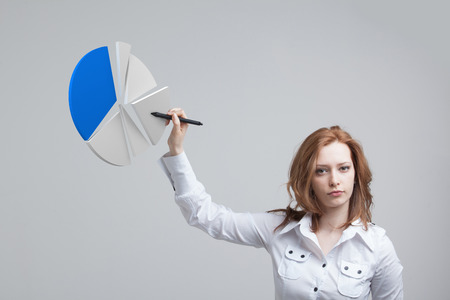 analytic: Young Businesswoman shows a pie chart (circle diagram). Business analytics concept. Stock Photo