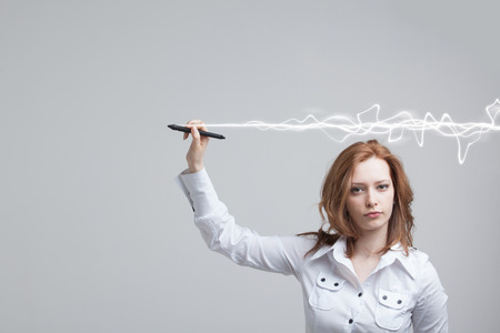 authors: Young woman making magic effect - flash lightning. The concept of copywriting or writing. Stock Photo