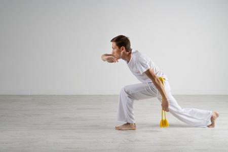 the acrobatics: El hombre joven que practica capoeira (arte marcial brasile�o con elementos de la danza, acrobacia y m�sica).