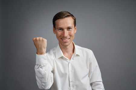 arms lifted up: Gesture of success. Happy smiling businessman in white shirt with raised hand. Half-length portrait. Stock Photo