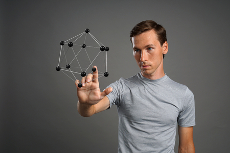 crystalline: Young man scientist working with model of molecule or crystal lattice on grey background.