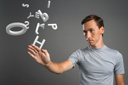 encode: Young man in t-shirt working with a set of letters on grey background, writing concept.