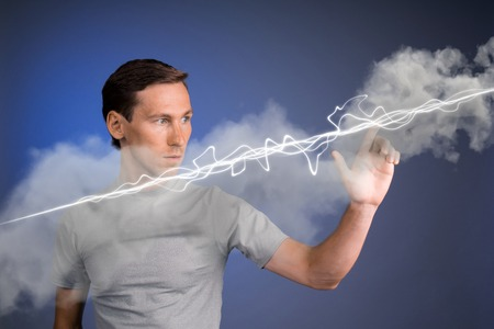 amperage: Young man making magic effect - flash lightning. The concept of electricity, high energy.