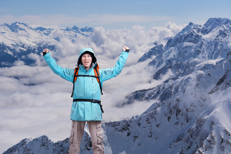 arms above head: Happy male mountain climber with arms raised above the head. In the background the high mountains. Portrait of a man on the topic of extreme mountaineering and success. Stock Photo