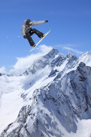 Snowboarder man jumping in snowy winter mountains. Extreme freeride. Stock Photo