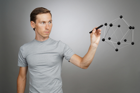 hormone  male: Young man scientist working with model of molecule or crystal lattice on grey background.