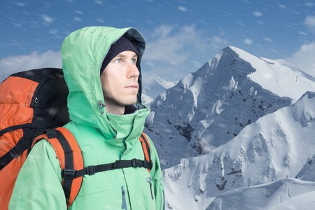 mountaineer: The mountaineer looks at the peak, standing against a winter snowy mountain landscape. Stock Photo