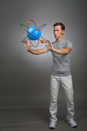 Young man scientist with atom model, research concept Stock Photo