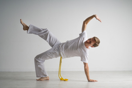 the acrobatics: Young Man practicing capoeira (brazilian martial art with elements of dance, acrobatics and music).