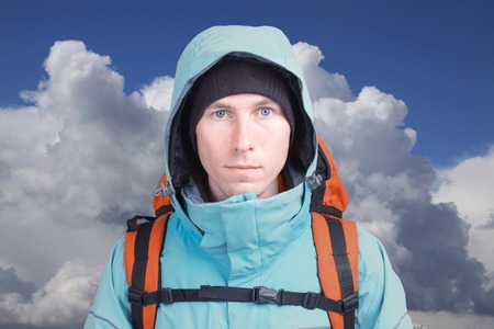 fullface: Hiker man with backpack in winter mountains with cloudy sky.