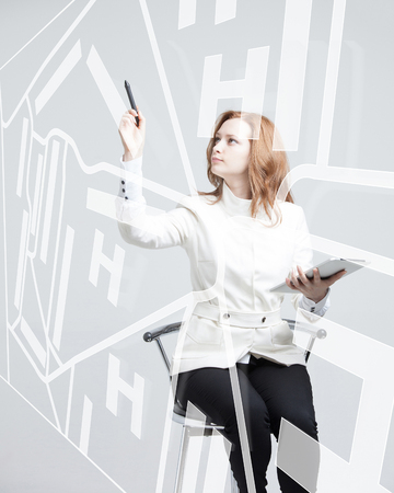 navigator: Future technology, navigation, location concept. Woman showing transparent screen with gps navigator map. Future technology, navigation, location concept. Woman showing transparent screen with gps navigator map. Grey background. Stock Photo