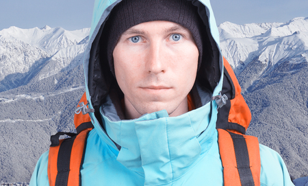 fullface: Hiker man with backpack in winter mountains.