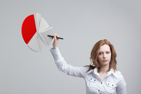 Young Businesswoman shows a pie chart (circle diagram). Business analytics concept. Stock Photo