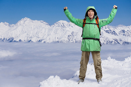arms above head: Happy male mountain climber with arms raised above the head. In the background the high mountains above the clouds. Portrait of a man on the topic of extreme mountaineering and success.